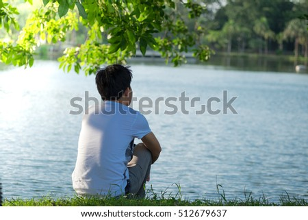 man sitting alone on the riverside