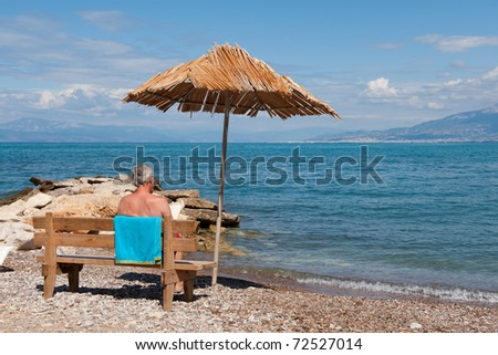 Man sitting and reading at a bench near the Greek beach