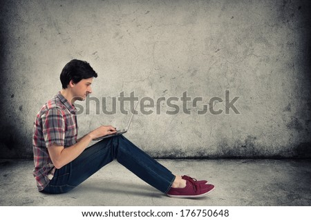 man sitting and using a laptop