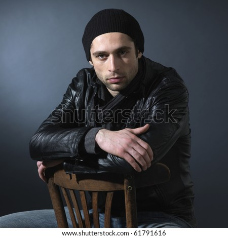 man sitting at a chair. Dark background. Square format.