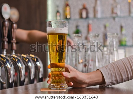 Man sitting at a counter in the bar holding a full pint glass of beer, close up view of his hand with the taps for dispensing draught beer alongside