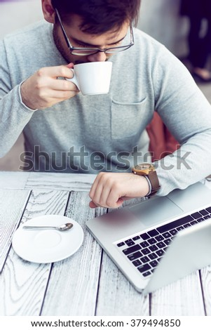 Man sitting at cafe bar, drinking morning coffee and looking at watch. - stock photo