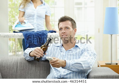 Man sitting at couch watching TV, woman ironing in the background. Selective focus on man. - stock photo