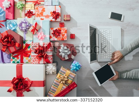 Man sitting at desk using a tablet and plenty of colorful gifts, celebrations and Christmas concept - stock photo