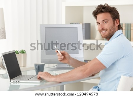 Man sitting at desk using laptop computer and phone at home, smiling at camera. Blank space on screens for your logo or image. - stock photo