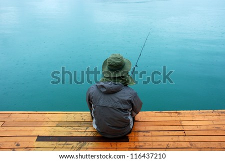 Man sitting at jetty fishing near lake during rainy day - stock photo