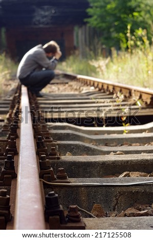Man sitting at railway track and tkinking about suicide. - stock photo