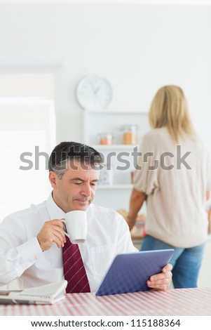 Man sitting at the kitchen holding a cup of coffee and using tablet pc before work - stock photo