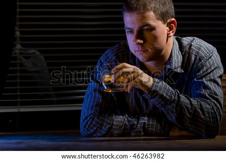 Man sitting at the office/home with a glass of whiskey - stock photo