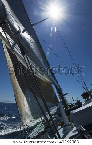 Man sitting by rigging and mast on sailboat deck at the ocean against blue sky and sun