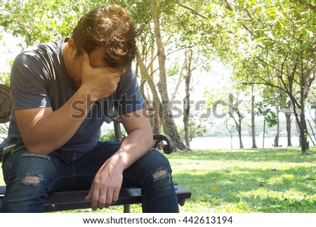 Man sitting dismal and hands off face in the park with sunshine