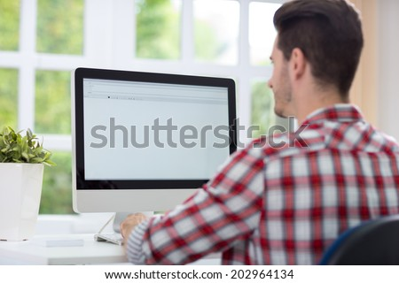 Man sitting front empty computer screen - stock photo