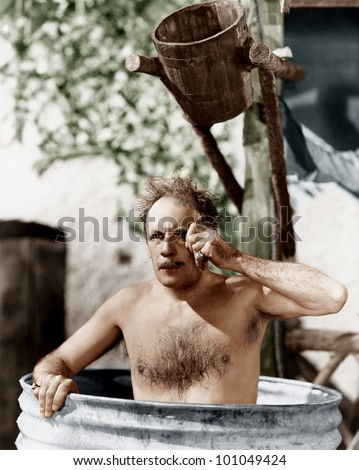 Man sitting in a barrel taking a bath and looking through his monocle