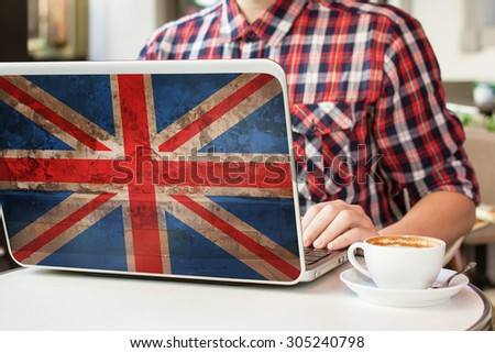 Man sitting in a cafe with cup of coffee and notebook with flag of Great Britain on it. English language learning concept - stock photo
