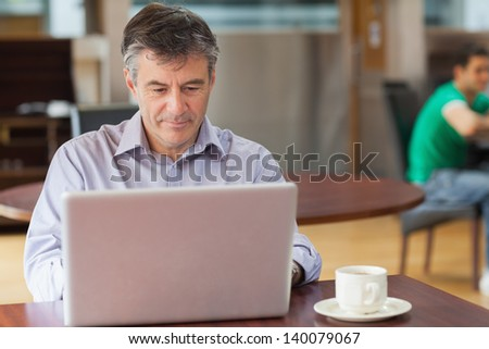 Man sitting in a coffee shop while drinking a cup of coffee and using a laptop