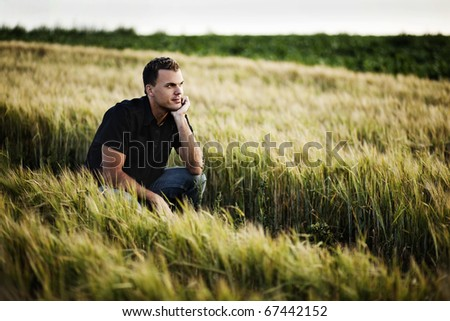Man sitting in a field, thoughtful.