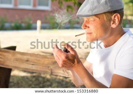 Man sitting in a park lighting up a cannabis joint clenched between his teeth with his lighter with copyspace - stock photo