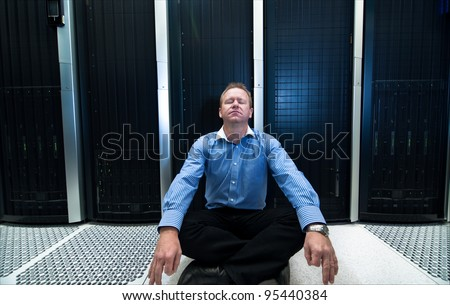 Man sitting in a relaxed meditation posture in front of computer/network data center equipment - stock photo