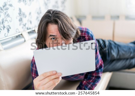Man sitting in a sofa using electronic tablet - stock photo