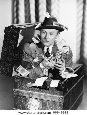 Man sitting in a trunk with money in his hands - stock photo
