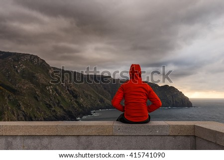 Man sitting in a wall. Cliffs in the seashore - stock photo