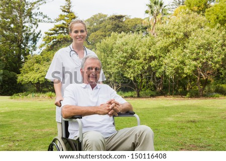 Man sitting in a wheelchair with his nurse pushing him outside in the park