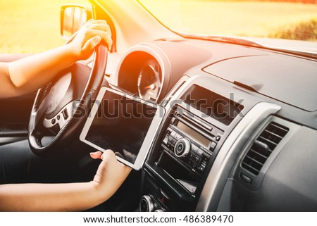 Man sitting in car and holding tablet with map gps navigation, toned at sunset.