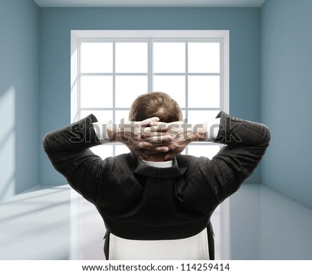 man sitting in chair in blue room