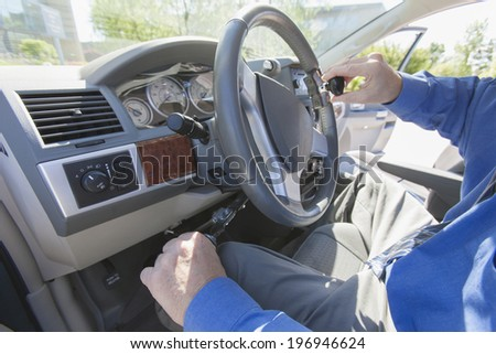 Man sitting in driver seat of accessible van with adaptive controls