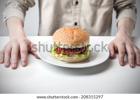 man sitting in front of a hamburger on a plate