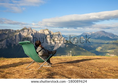 Man sitting in lounge chair with mountain view - stock photo