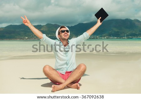 man sitting in sand with legs crossed showing victory sign and holding an ipad in hand, celebrating success - stock photo