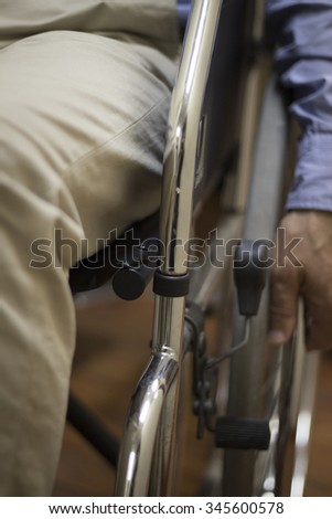 Man sitting in shiny steel metal wheel chair wearing blue shirt pushing wheel to move himself forward in hospital clinic. Color digital photo in warm tones shot from in front