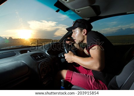 man sitting in the car and Edith among woods and fields at sunset. - stock photo
