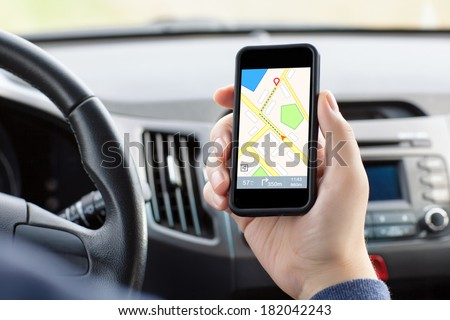 man sitting in the car and holding a touch phone with interface navigator on a screen