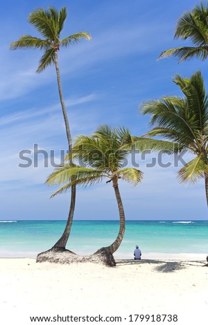 Man sitting in the shade of some palm trees on a caribbean beach in front of the blue ocean - stock photo