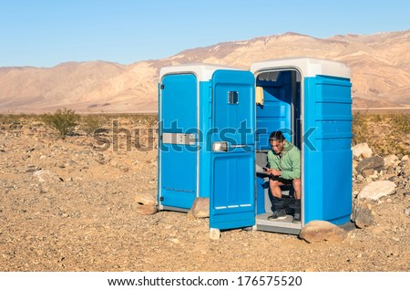 Man sitting in the Toilet in the middle of the desert - Death Valley California - stock photo