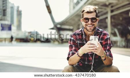 Man Sitting Listening Music Earphones Concept - stock photo