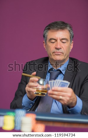 Man sitting looking at his cards holding a cigar