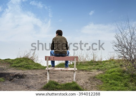 Man sitting on a bench and looking at the sea