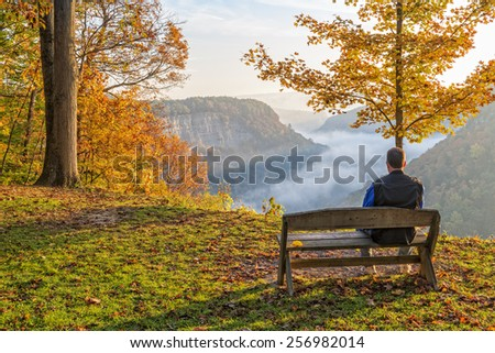 Man Sitting On A Bench Enjoying An Early Morning Sunrise At Letchworth State Park - stock photo