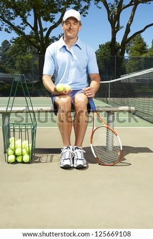 man sitting on a bench holding tennis balls with his left hand, tennis racket leaning against the bench, net visible on his right side, trees in the background - stock photo