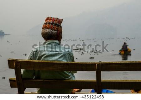 Man sitting on a bench near lake Begnas, Nepal - stock photo