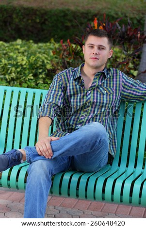 Man sitting on a bench with legs crossed - stock photo