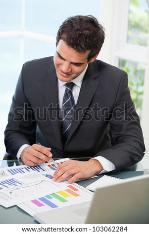 Man sitting on a chair while looking at graph in an office - stock photo