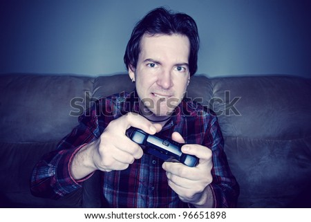 Man sitting on a couch playing video games in a dark room - stock photo