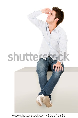 Man sitting on a cube and looking away - isolated over white - stock photo