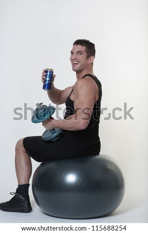 man sitting on a gym ball being tempted to give up and have a drink - stock photo
