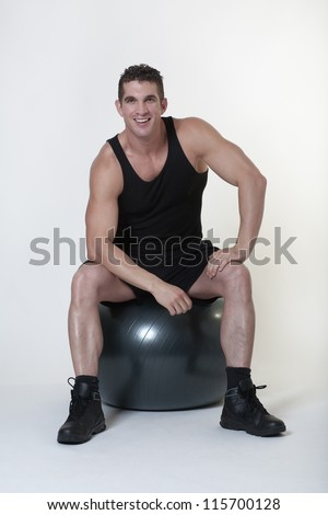 man sitting on a gym ball looking at camera with a big smile on his face - stock photo