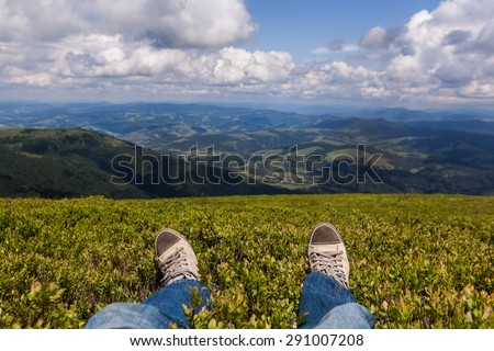 Man sitting on a high mountain top with first person perspective view, legs in focus - stock photo